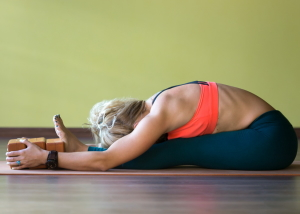 Sporty beautiful young blond woman in sportswear working out indoors doing exercise for spine shoulders hamstrings sitting in paschimothanasana pose seated forward bend posture using wood bricks