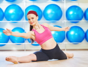 fitness woman instructor doing stretching pilates exercises split in sport club